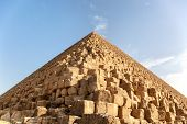 Closeup detail of a Pyramid, Giza, Egypt, against blue sky. The Great Pyramid of Giza is the only remaining of the original Seven Wonders of the world.