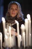 Beautiful woman prays, stands behind candles