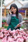 Black-haired woman calling while doing stocktaking in garden centre