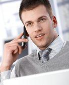 Bem parecido jovem empresário falando no telefone celular.