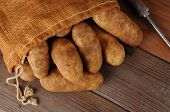 An overhead view of a burlap sack of potatoes on a rustic wooden background.