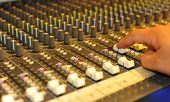 Close-up of sound engineer's hand moving sliders on audio mixing board