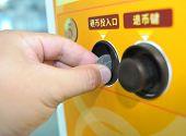 Close-up Hand holding a coin input self service machine