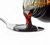 stock photo of cough syrup  - bottle pouring cough syrup into a spoon - JPG