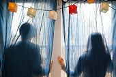Silhouette Of Young Couple Behind Blue Curtains