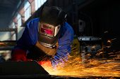 worker grinding/welding metal and sparks spreading