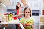 picture of three sisters  - Portrait of happy girl with vegetable salad on background of her mother and sister cooking - JPG