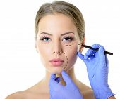 Beautiful woman ready for cosmetic surgery, female face with doctor's hands with pencil, over white
