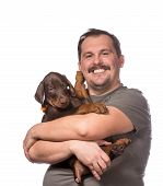 stock photo of doberman pinscher  - Young man is holding his sweet doberman puppy isolated on white background - JPG