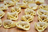 Raw Tortellini on wooden background