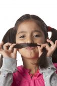 Little girl is making a moustache of her hair