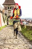stock photo of prophets  - A gypsy girl runs up a medieval way and swings prophet accessories - JPG