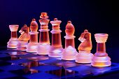Glass chess on a chessboard lit by a blue and orange light