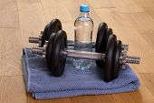 Dumbbells and bottle of water in a gym