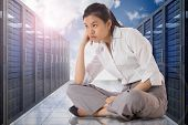 Businesswoman sitting cross legged against server hallway in the sky