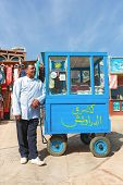 DAHAB, EGYPT - JANUARY 29, 2011: Vendor on the street next to stand. Street food is the cheapest way
