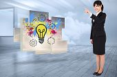 Smiling businesswoman pointing against room with holographic cloud