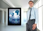Happy businessman standing with hand in pocket against white room with screen