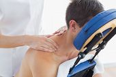 Man receiving shoulder massage by female therapist on massage chair in hospital