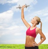 fitness and diet concept - young sporty woman lifting steel dumbbell