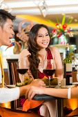 Asian Chinese business people having dinner in elegant club restaurant or hotel