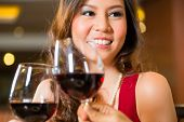 Chinese woman toasting in a restaurant with red wine and a wine glass