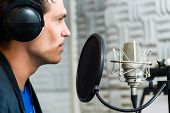 Young male singer or musician with microphone and headphone for audio recording in the Studio