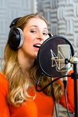 pic of singer  - Young female singer or musician with microphone and headphone for audio recording in the Studio - JPG