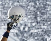 image of football helmet  - A football player raises his helmet in triumph with a simple stadium crowd background - JPG