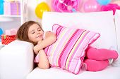 Pretty little girl slipping on sofa on celebratory background