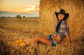 stock photo of cowgirl  - Beautiful Cowgirl in hay - JPG