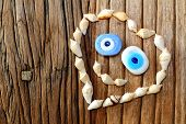 Creative shape of heart with sea shell and amulet smiling on a wooden table backround