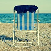 a deckchair and a man swimsuit on the beach, with a retro effect