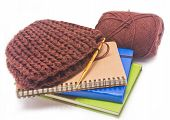 Brown crochet hat with golden hook yarns and books.