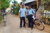 WELIGAMA, SRI LANKA - MARCH 8, 2014: Two postmen delivering post to local people. Sri Lanka Posts ha