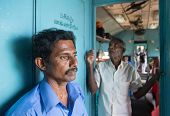 HIKKADUWA, SRI LANKA - MARCH 12, 2014: Two local men standing in train. Trains are very cheap and po