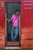 HIKKADUWA, SRI LANKA - MARCH 12, 2014: Local man standing at wagon entrance. Trains are very cheap a