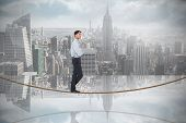 Serious asian businessman on tightrope against room with large window looking on city