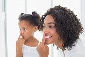 Pretty mother putting face cream on with her daughter at home in the bathroom
