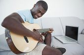Casual man sitting on sofa playing the guitar with laptop at home in the living room