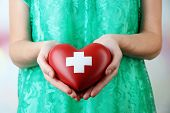 Red heart with cross sign in female hand, close-up, on light background