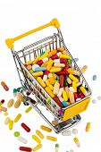 colorful tablets in the shopping cart icon photo for healthcare costs, pharmacies, abundance of drugs