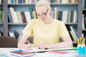 Happy student with glasses writing in library