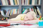 Tired student sleeping in library