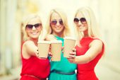 beverage and drink concept - three smiling blonds holding takeaway coffee cups in the city