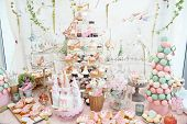 Wedding decoration with pastel colored cupcakes, meringues, muffins and macarons. Elegant