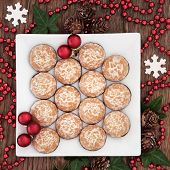 Christmas biscuit background with snowflakes, winter greenery and red bauble decorations over old oak wood table.