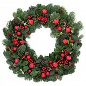 Christmas wreath with red bauble decorations, holly, ivy, mistletoe, fir and pine cones over white background.