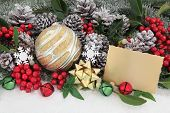 Christmas scene with bauble decorations, gift tag, holly and winter greenery over snow background.