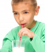 Cute little boy drinks milk using drinking straw, isolated over white